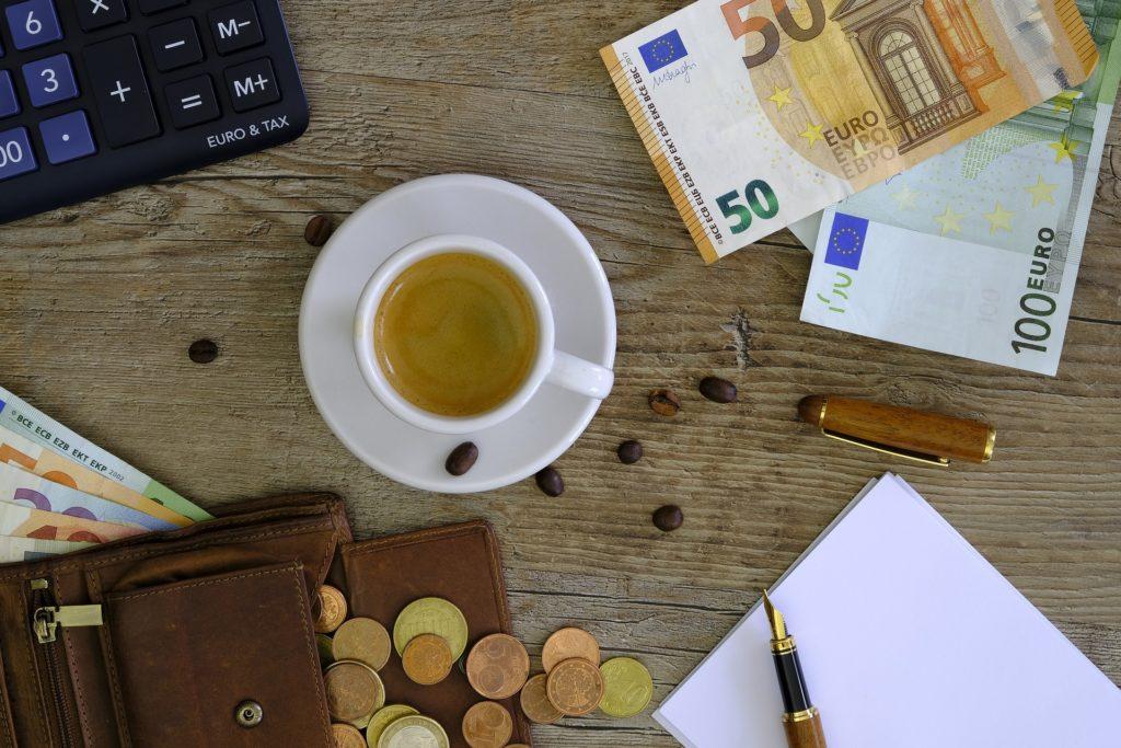Geld auf dem Tisch neben einer Kaffeetasse