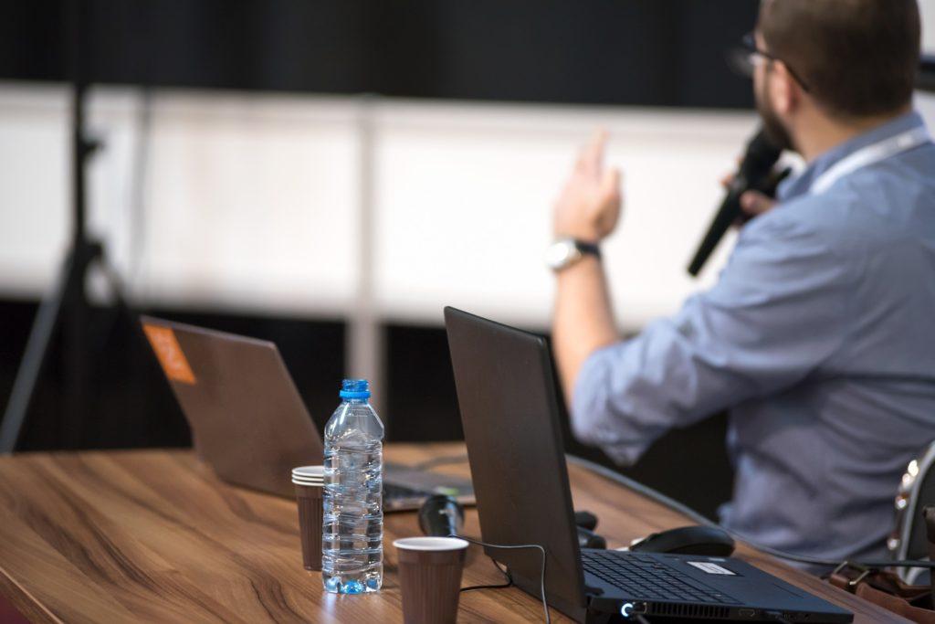Eine Wasserflasche neben zwei Laptos auf einem Tisch